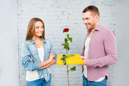 congratulating: Smiling man congratulating his girlfriend with rose and gift