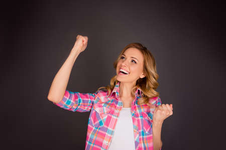 triumphing: Successful pretty  woman triumphing with raised fists