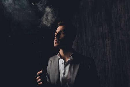 Erfolgreicher Geschäftsmann mit Zigarre und Rauch auf schwarzem Hintergrund Standard-Bild