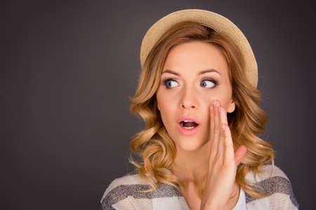 Portret van mooie roddel in hoed bedrijf hand in de buurt gezicht en geheim vertellen