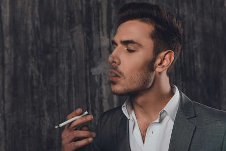 work addicted: Side view of a cheeky man in suit on the grey background smoking a cigarette