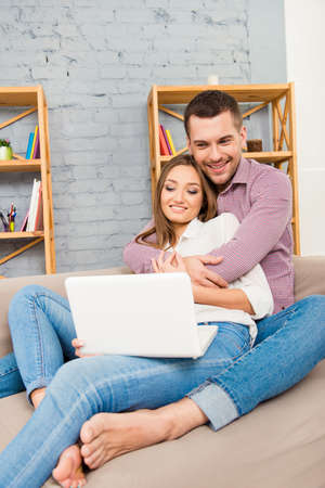 Handsome man embracing his girlfriend sitting on sofa with laptop