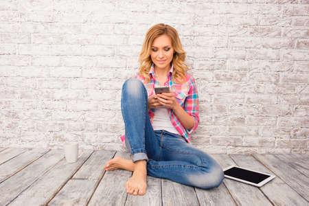 맨발의 여자 바닥에 앉아 스마트 폰에 메시지를 입력