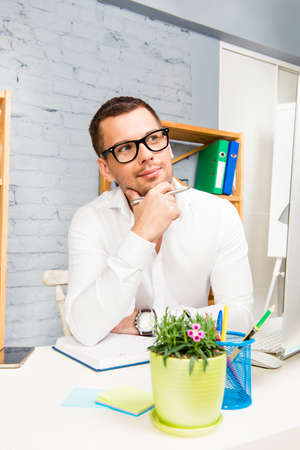 minded: Portrait of minded young businessman in glasses sitting in office