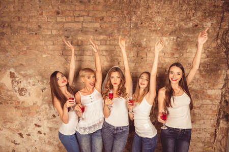 stemware: Cute girls celebrating hen-party with raised hands and stemware