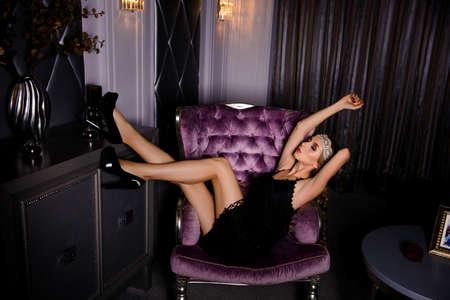 dishy: Sedutive woman in black dress and high heel shoes sitting on  armchair Stock Photo
