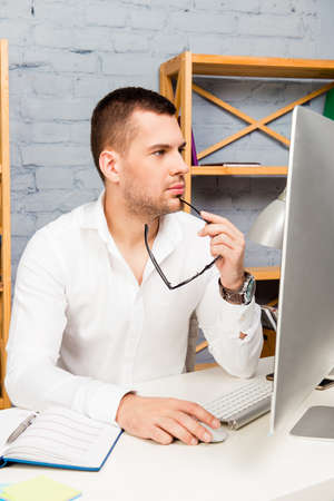 minded: Young minded businessman with glasses  at the workplace working with computer Stock Photo