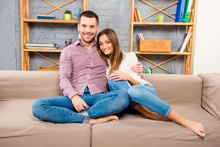 Two cheerful lovers sitting barefoot on the couch and huging