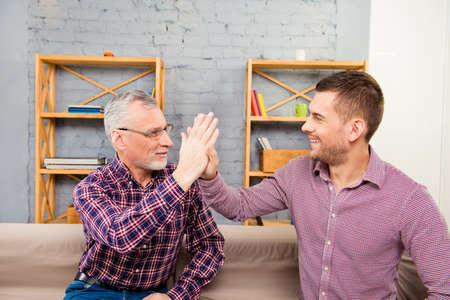 Knappe bejaarde vader het geven van een high five aan zijn zoon