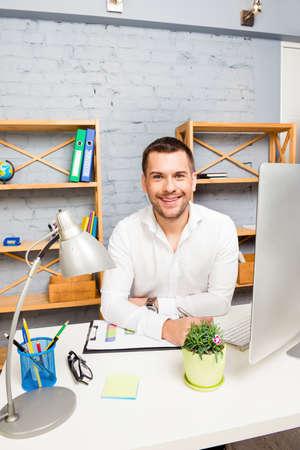 trabajando duro: hombre de negocios joven alegre que trabaja duro en la oficina