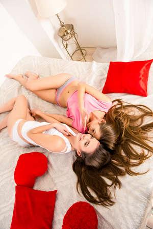 pijamada: chicas alegres en pijamas chismosas y acostado en la cama de la mano