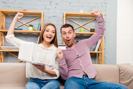 family and friends: Cheerful family making internet shopping with laptop and bank card Stock Photo
