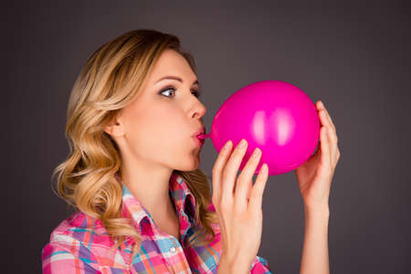 Side view portrait of pretty woman blowing balloon