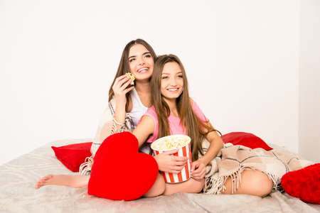 lesbo: Happy girls watching film in bedroom and eating popcorn