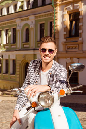 moped: Cheerful young man in spectacles with moped and cup of coffee