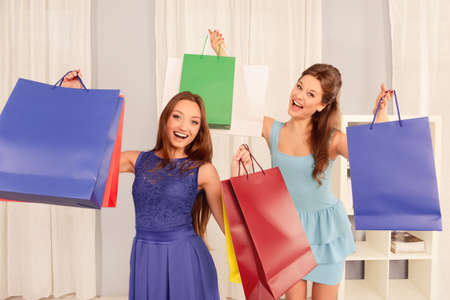 lesbo: Two happy cheerful girls demonstrating their purchases Stock Photo