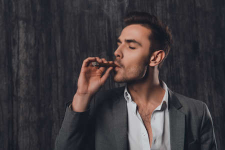 handome: Handome brutal man in suit on the gray background smoking a cigar
