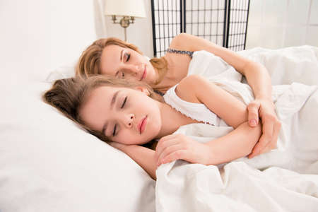 mum and child: Close up photo of  happy  mother and child daughter sleeping in bed embracing