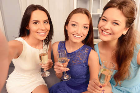making dresses: Pretty girls holding glasses with champagne and making selfie Stock Photo