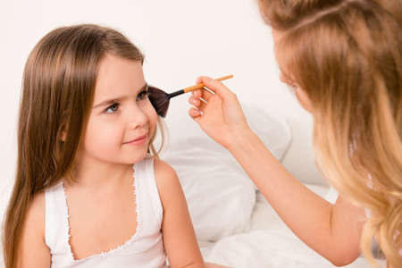 maquillage: Close up portrait of woman doing maquillage to her cute daughter Stock Photo