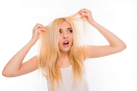 damaged: Surprised unhappy young woman looking at her damaged hair