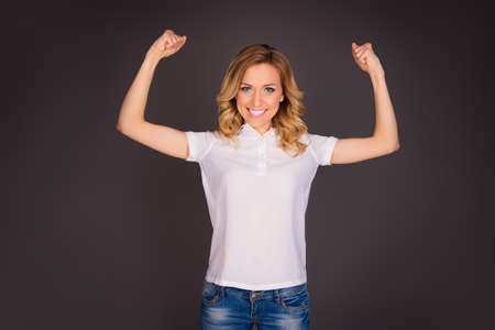 Young happy sexy woman showing her muscles