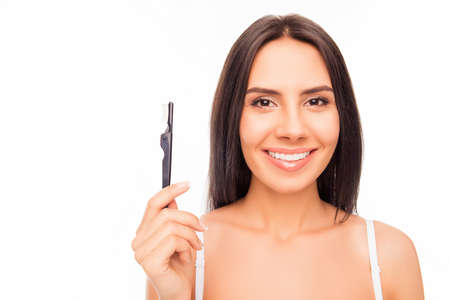 brash: Cheerful young brunette holding brash of mascara on white background