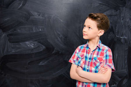Young boy with crossed hands near chalkboard at school
