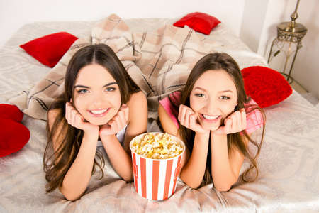 lesbo: Close up photo of two sisters lying in bed with popcorn and smiling