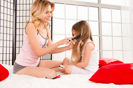 combing hair: Caring young mother combing hair of her little daughter
