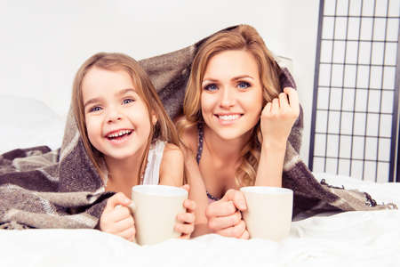 Portrait of happy daughter and mother lying under plaid with cups of tea Stock Photo