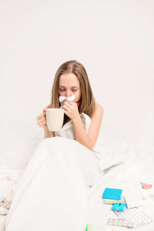 rheum: Sick woman with rheum sitting in bed and holding a cup of tea Stock Photo