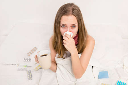 rheum: Sick woman with rheum holding a cup of hot tea