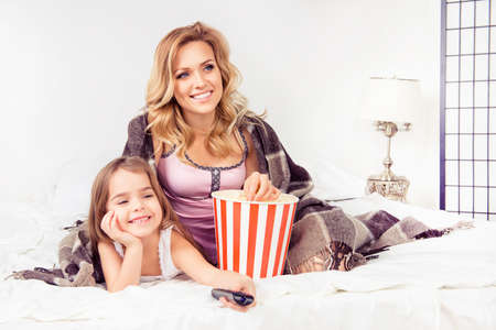 mom and daughter: Portrait of happy daughter and mother watching cartoons with popcorn Stock Photo