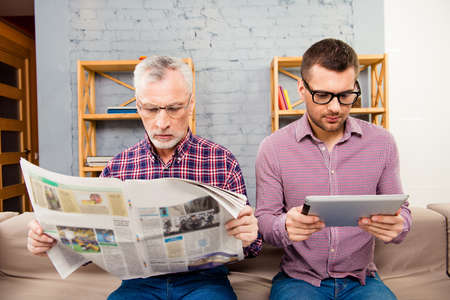 Old father reading newspaper and his son using tablet