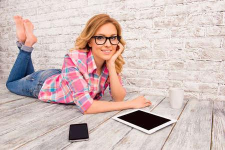 タブレットと電話が付いている床に、裸足が横になっている眼鏡で幸せな若い女 写真素材