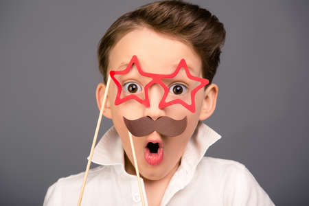 Close up portrait of surprised funny schoolboy holding props Stock Photo