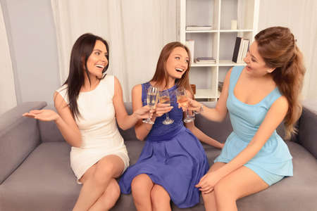 clinking: Three attractive young girlfriends celebrating with champagne and clinking Stock Photo