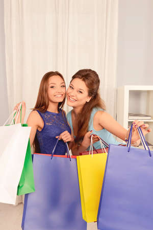 lesbo: Cheerful attractive young shoppers showing color packages