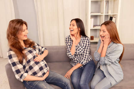 attractive pregnant: Pregnant woman and her friends sitting on sofa and laughing