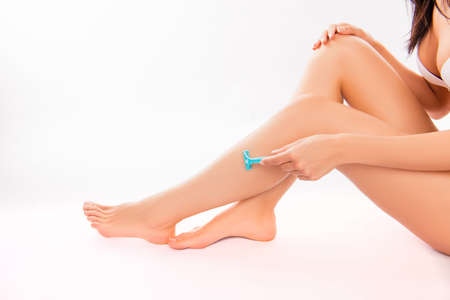 depilate: Closeup photo of young  woman shaving her leg with blue razor Stock Photo