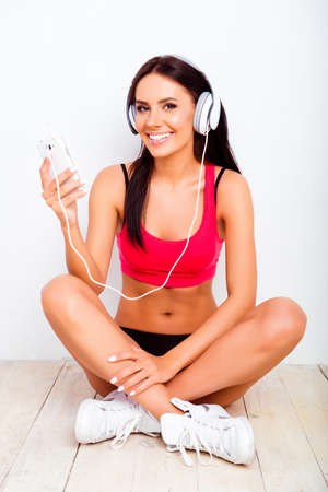 crossing legs: girl sitting on the floor with crossing legs and listening music with headphones