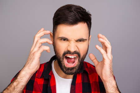 bad temper: Handsome depressed young man screaming and showing hands