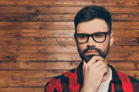 to ponder: Portrait of ponder young man in glasses on backgroung of wooden wall