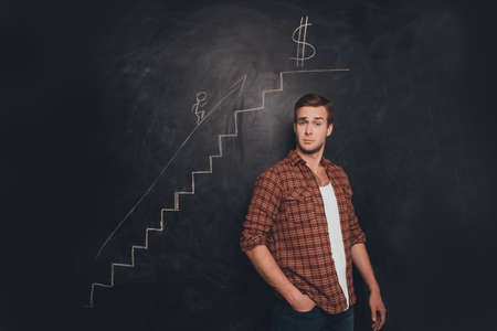 Succseful young man against chalkboard reaching the goal to become rich