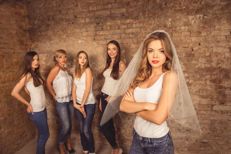 bridesmaids: Beautiful bride with crossed hands standing in front of her bridesmaids Stock Photo