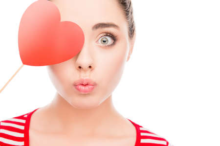 pouting: Funny woman holding paper heart near eyes and pouting Stock Photo