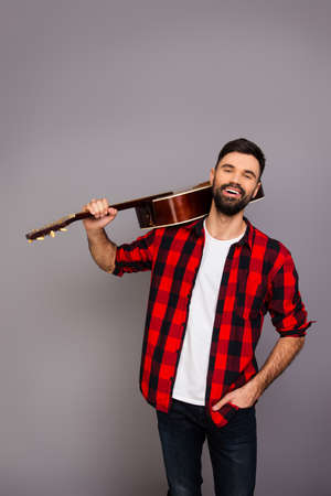 instrumentalist: Portrait of happy smiling man holding guitar on shoulder Stock Photo