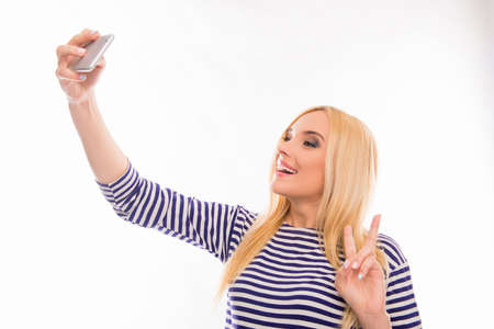 two fingers: Happy smiling girl making selfie and gesturing with two fingers