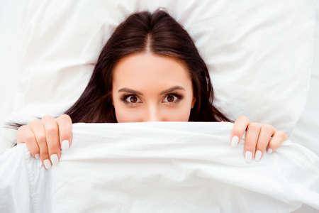 coverlet: Funny flirting girl hiding her face white coverlet Stock Photo